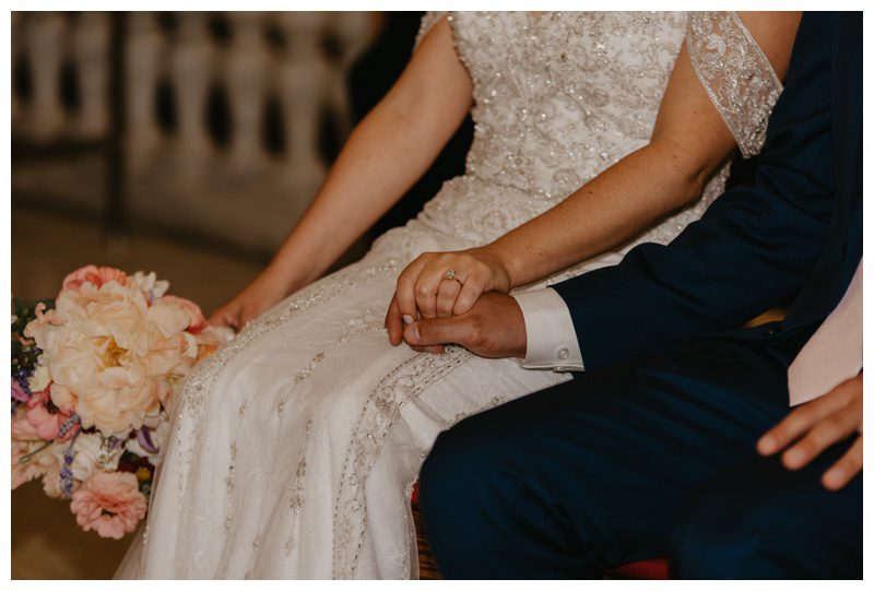 Bride and groom hold hands during church wedding ceremony