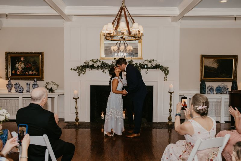 First Kiss by fireplace in New Jersey - greenery white florals and candles