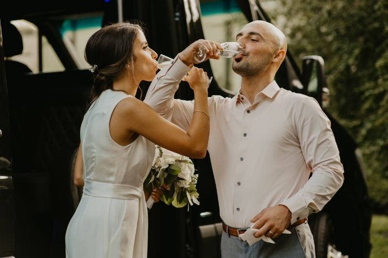 bride and groom popping champagne before backyard wedding reception in new jersey