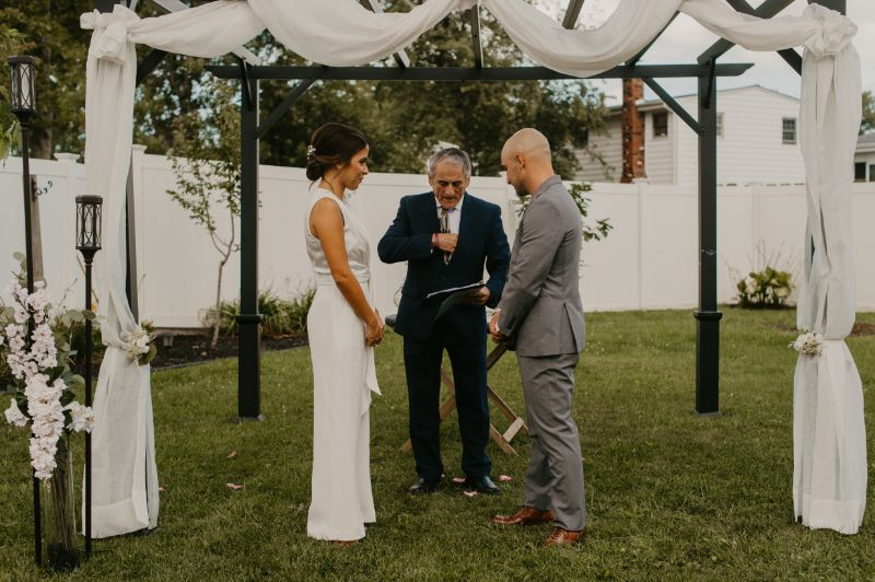 Backyard wedding ceremony with bride groom and officiant