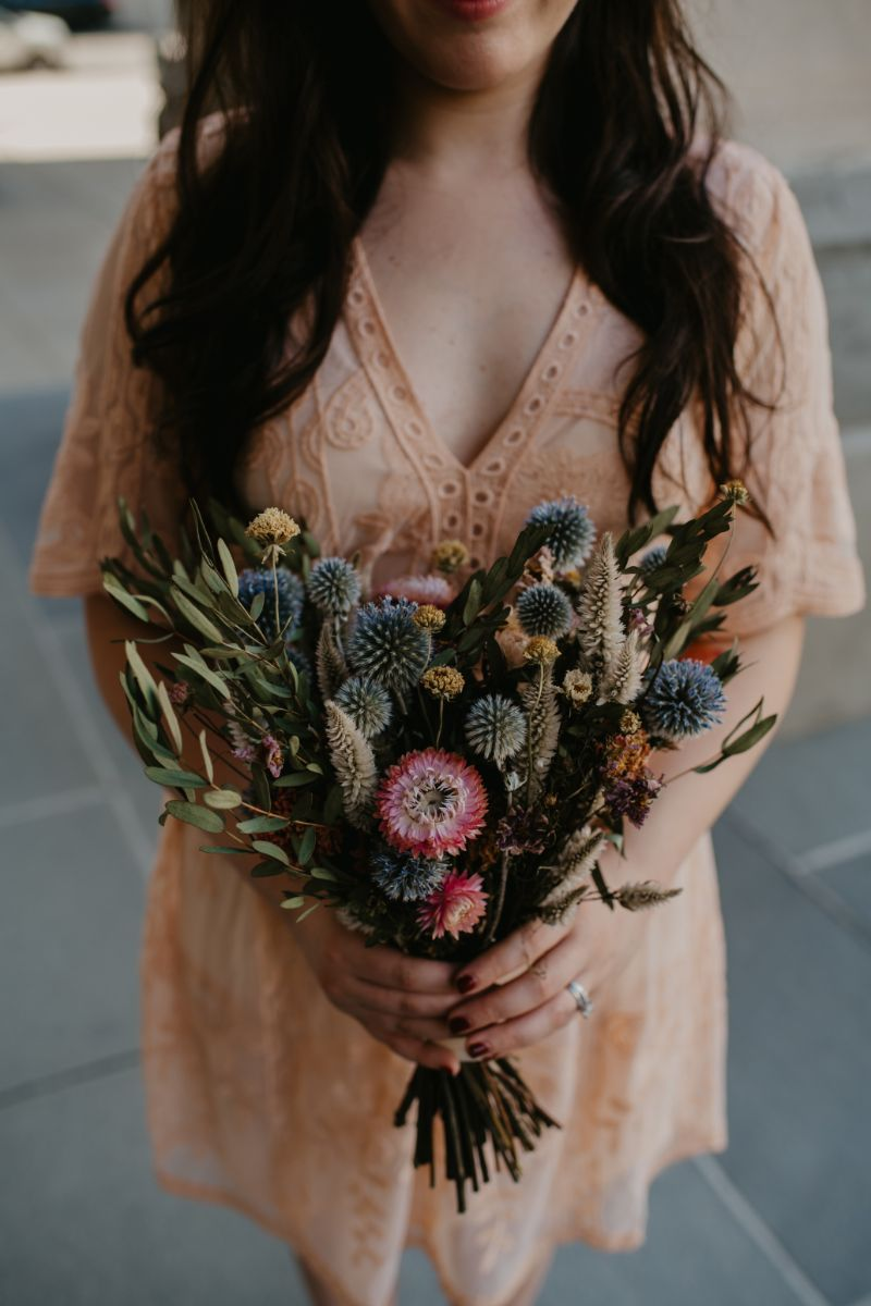bride in peach dress and wildflower bridal bouquet
