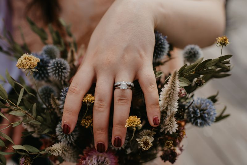 stunning bouquet of wildflowers with wedding ring and maroon nail polish