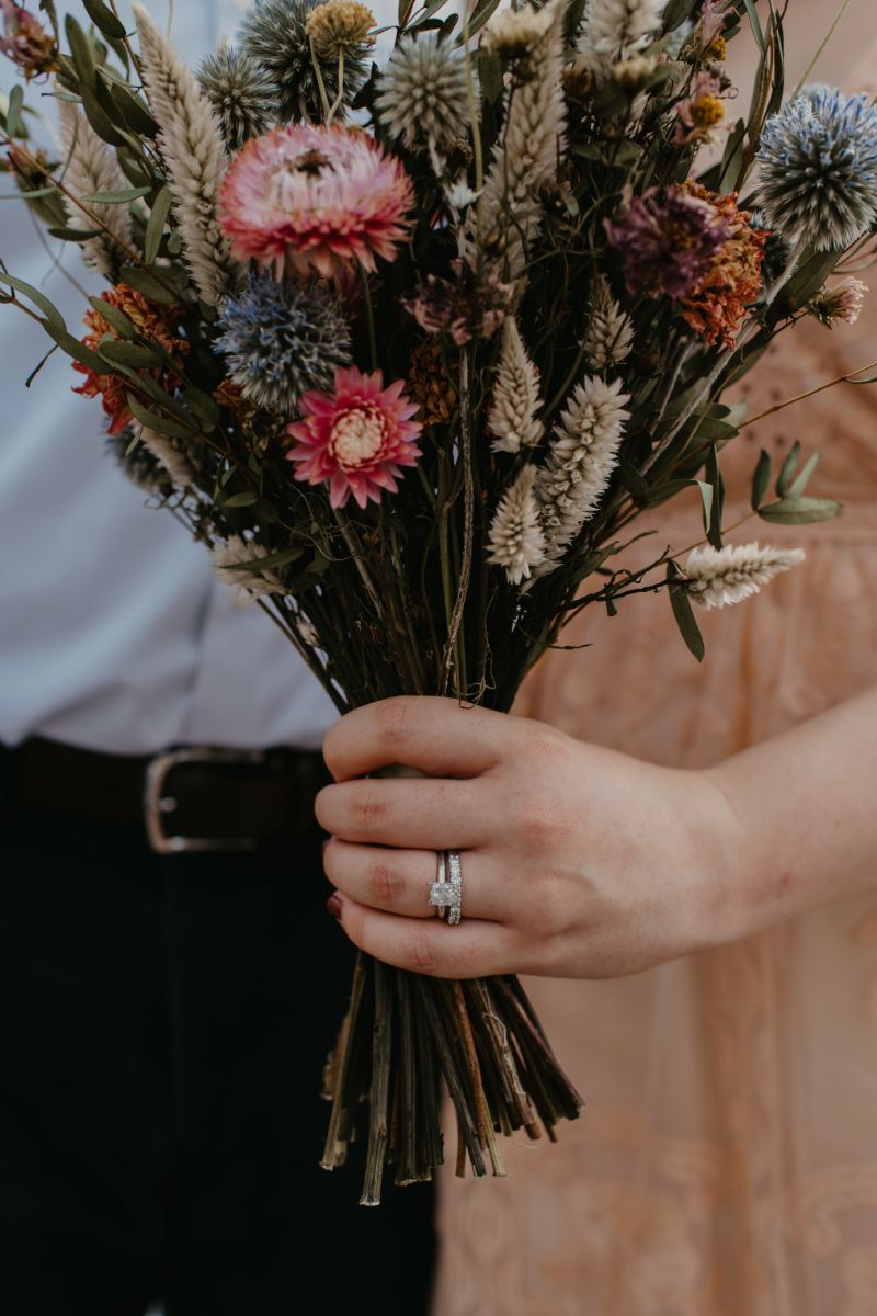 wedding rings on bride while holding a bouquet