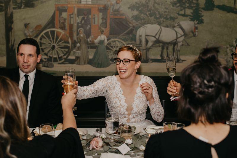 Bride toasting with champagne at Aurora Inn wedding reception
