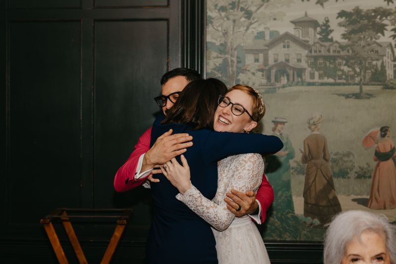 Bride and groom hugging mother of groom after toasts
