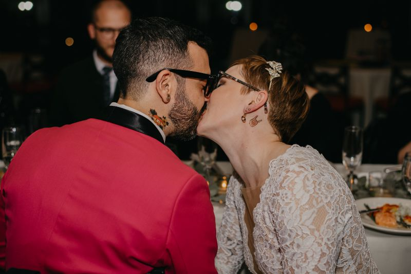 Bride and groom kissing at wedding reception table with tattoos