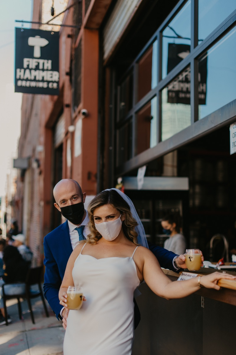 Bride and groom standing with beers in Long Island City