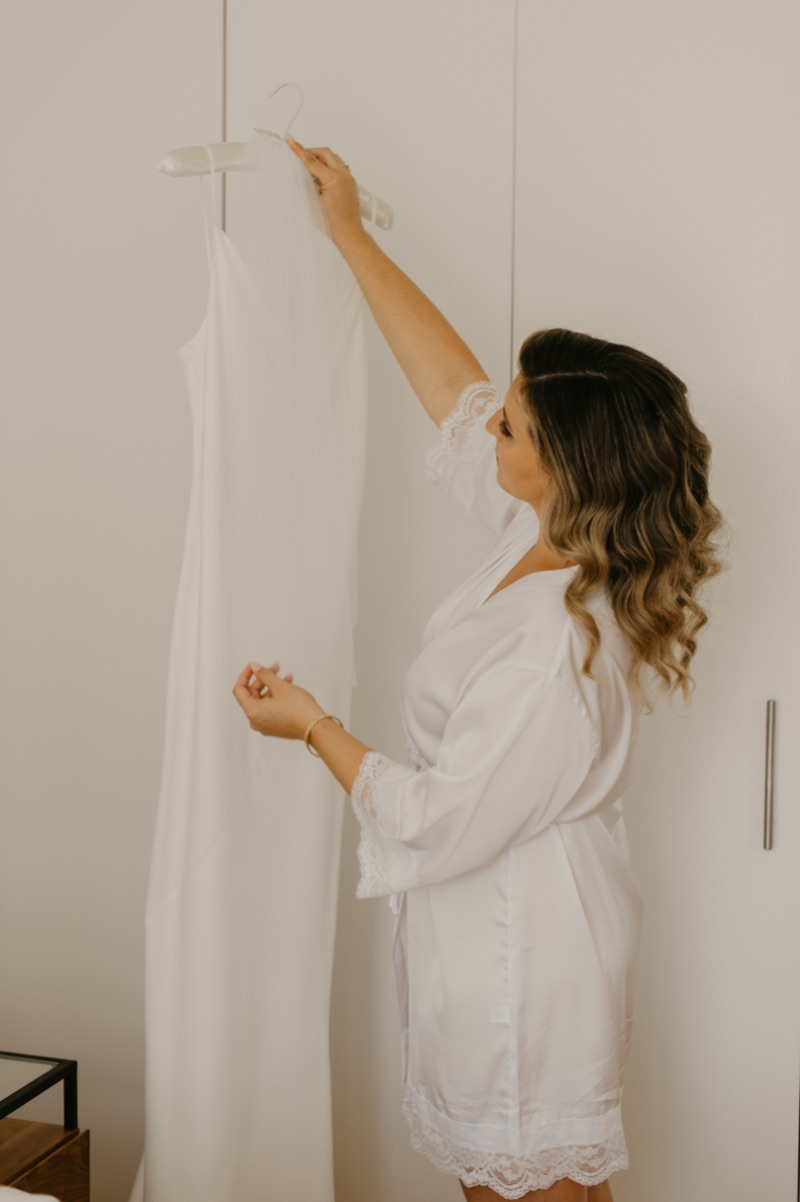 Bride hanging up wedding dress in New York apartment