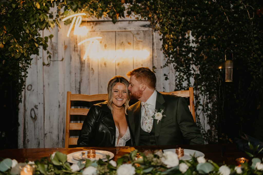 Backyard wedding in New Jersey with groom kissing bride at sweetheart table