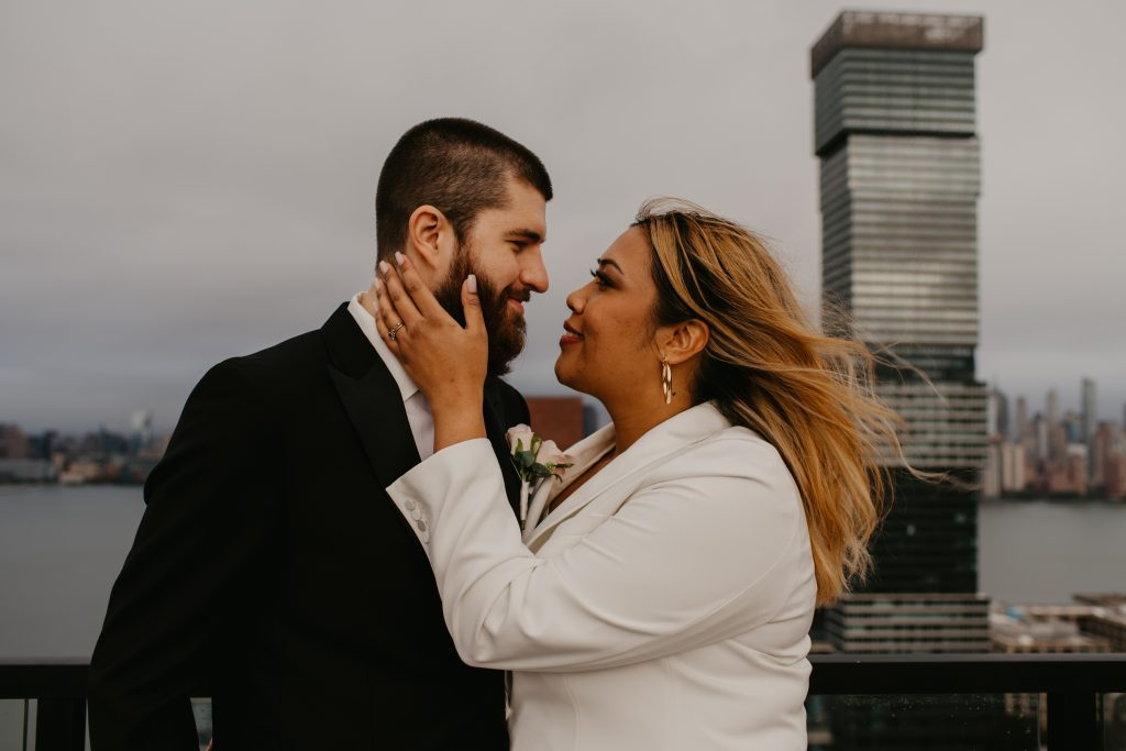 Bride looks groom in the eye in front of Hoboken skyline