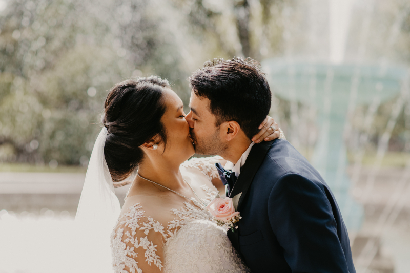 Bride and groom kiss in front of the fountain