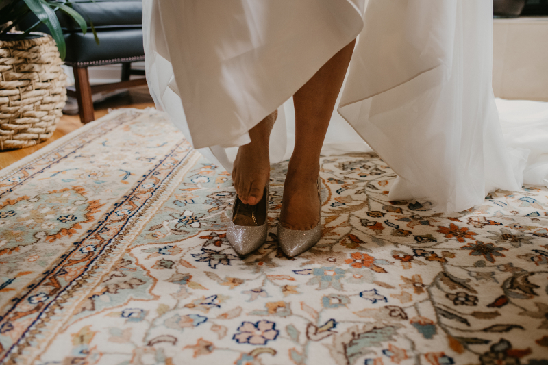 Bride in wedding dress putting shoes