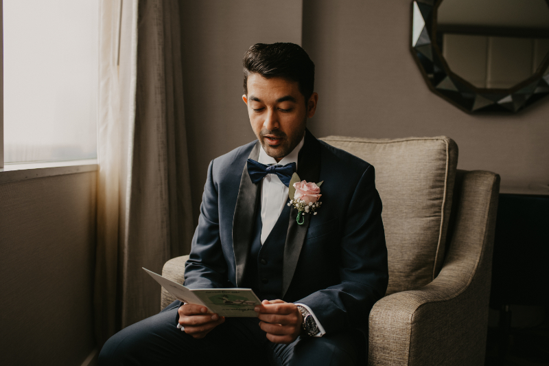 Groom reading letter from bride before the wedding