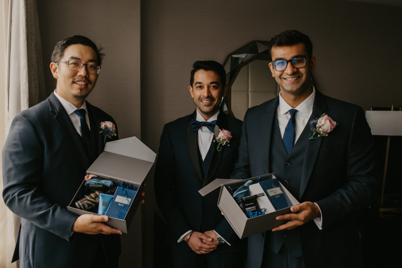 Groom standing with best man and father in law holding groom gift boxes