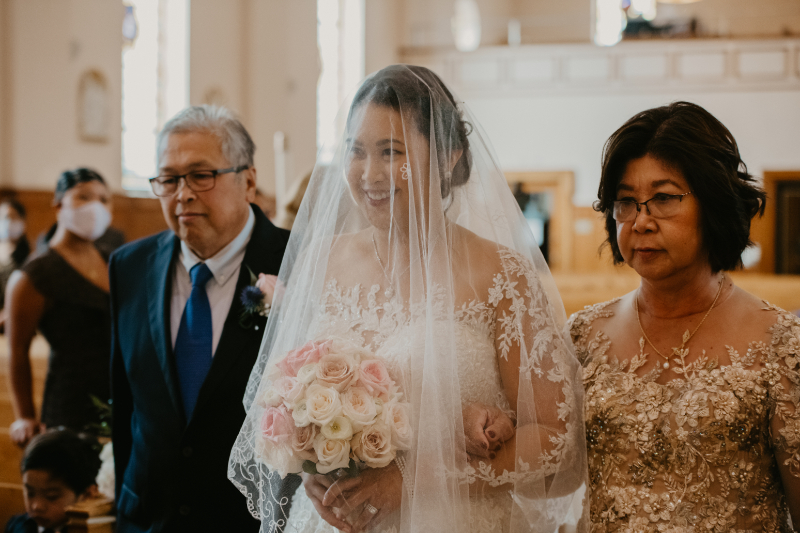 Bride walking down the aisle at Our Lady of Most Carmel with her parents