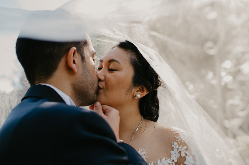 Bride and groom kiss under their veil