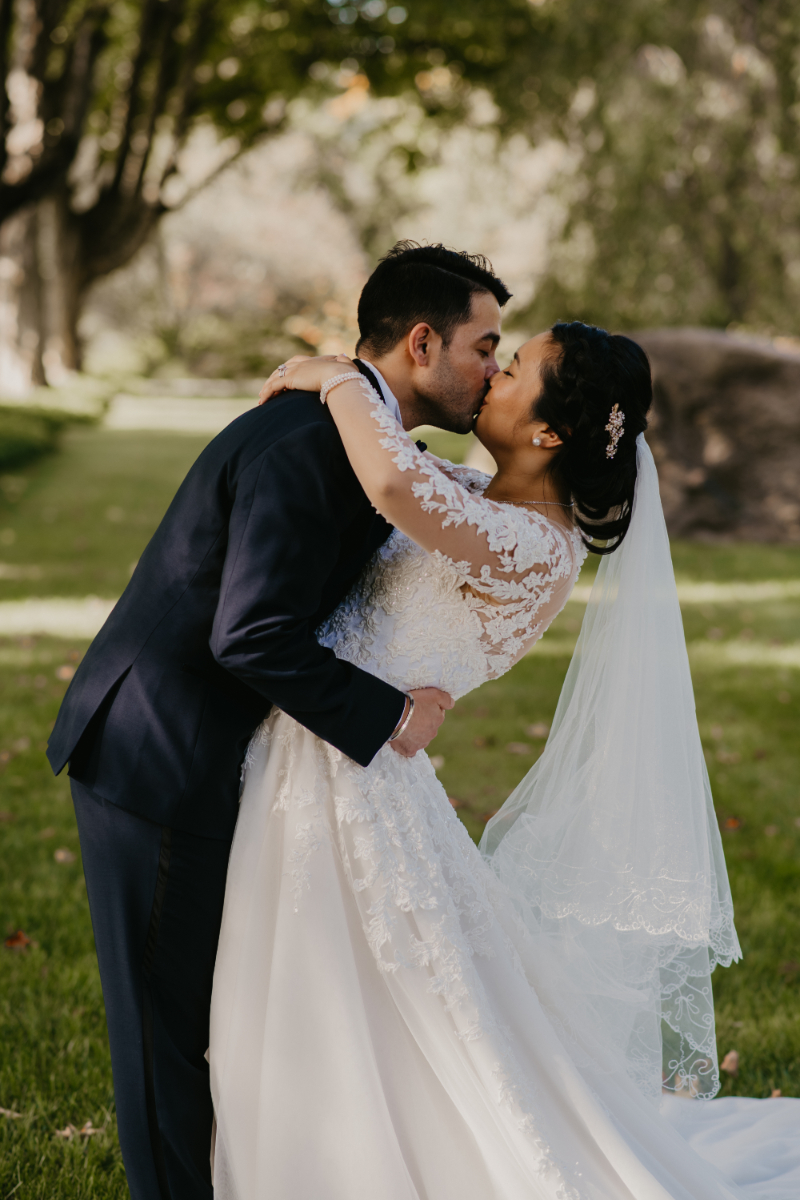 Bride and groom kissing during outdoor photos
