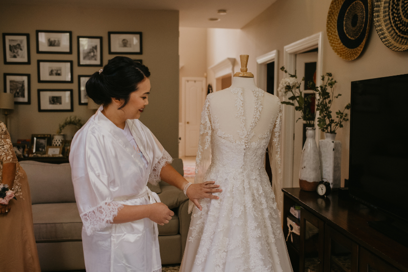 Bride looking at her wedding dress on her wedding day
