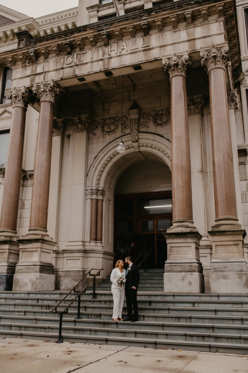 Bride and Groom pose outside city hall after elopement
