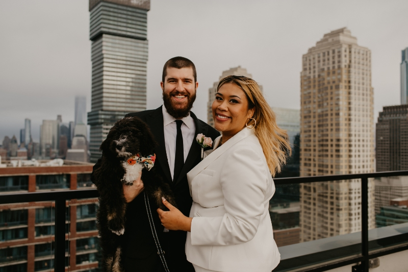 bride and groom pose with dog on rooftop of their apartment