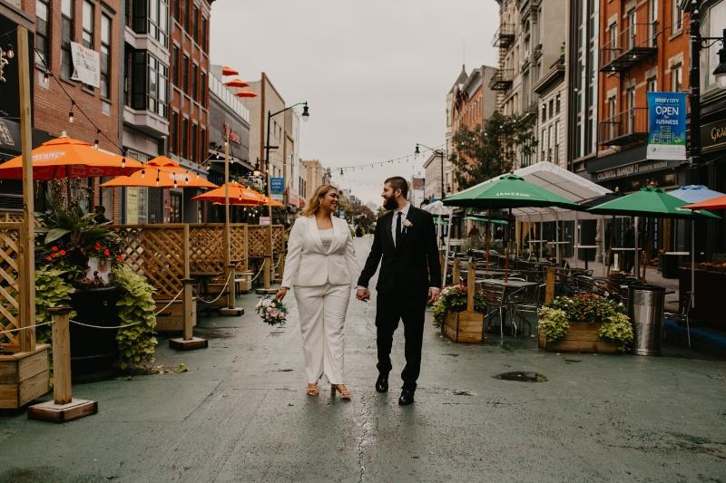 Bride and groom walk down Jersey City pedestrian walkway