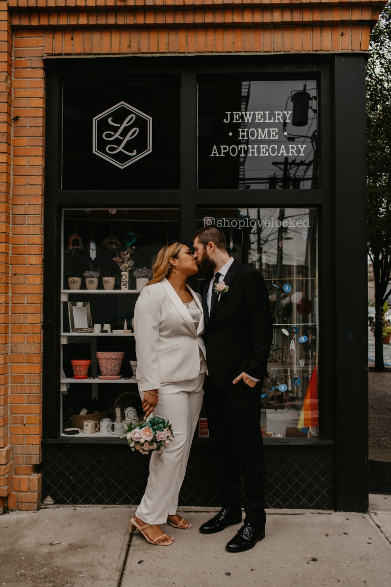 Bride and groom pose in front of Love Locked - their favorite jewelry store in Jersey City where they purchased their wedding bands