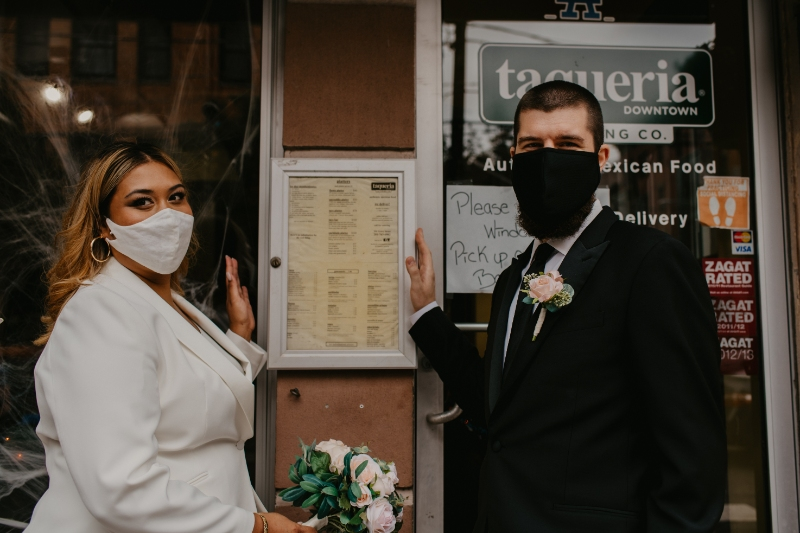 Bride and groom pose next to favorite taco place