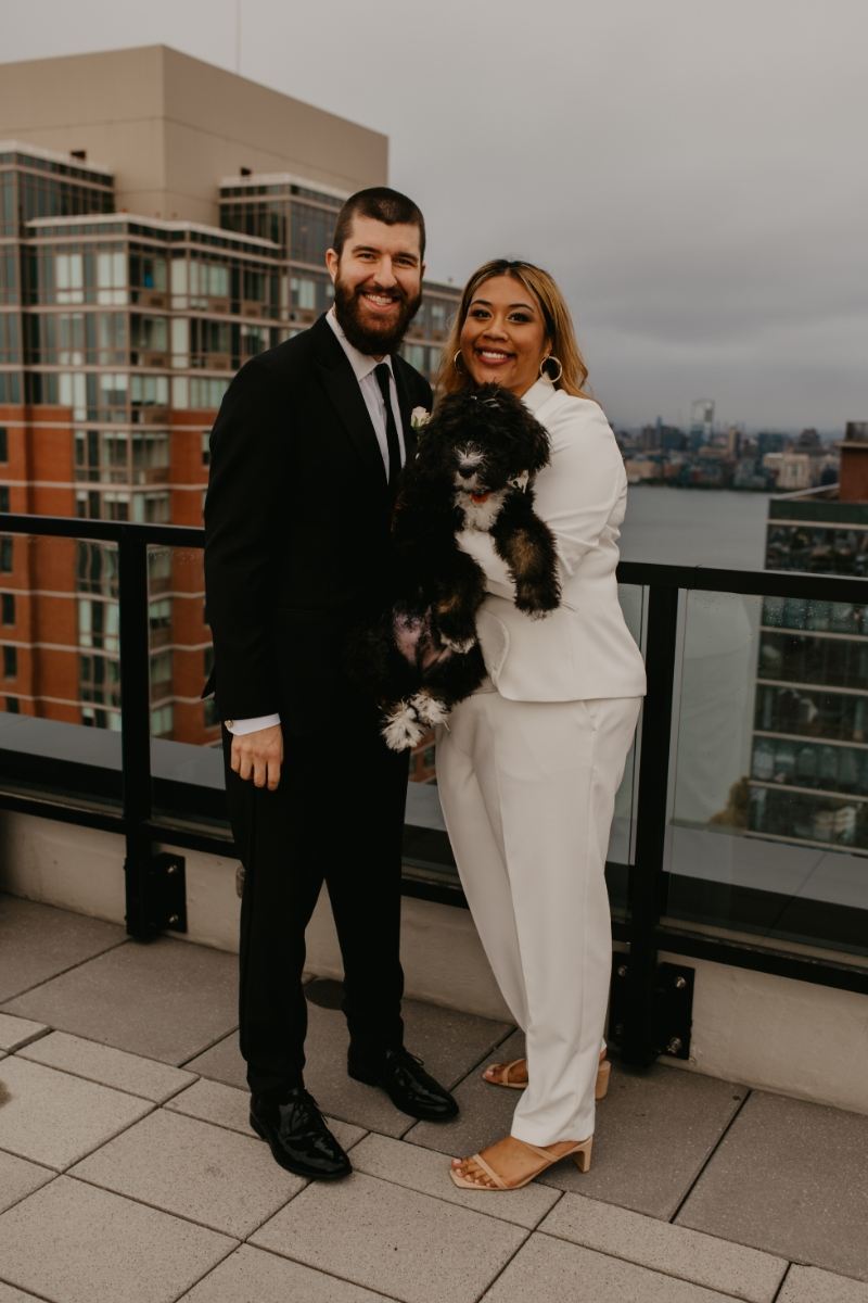 bride holds dog with groom on rooftop overlooking Jersey city
