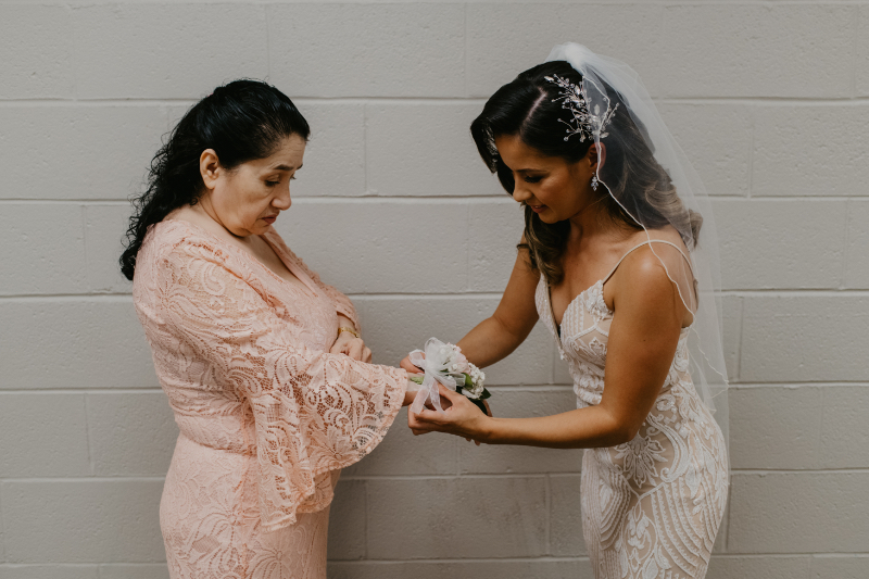 Bride slips corsage on her mother before the ceremony