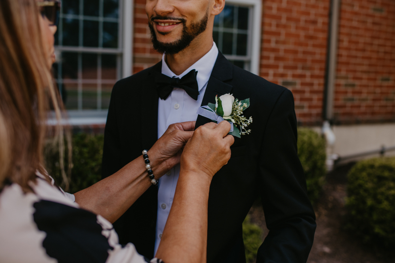 Groom's mother pins on his boutonniere after the church ceremony in New Jersey