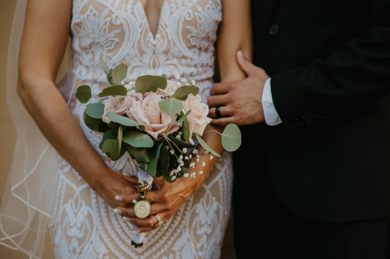 bride in lace dress with veil holds onto her bouquet with a brooch emblem