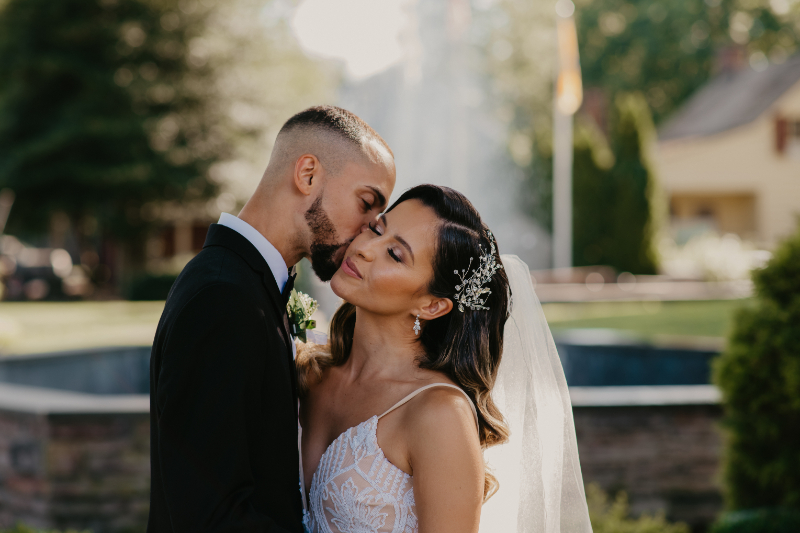 groom kisses bride on the head outside of New Jersey fountain