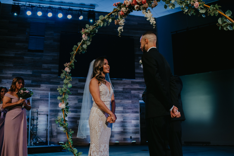 Bride looks at groom at the church wedding altar