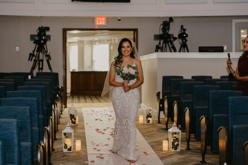 Bride walks down the aisle smiling at the groom