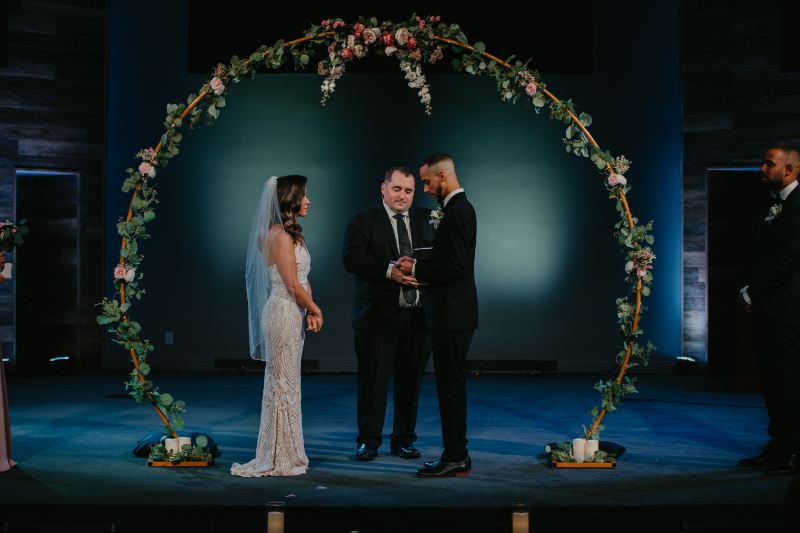 wedding flowers and greenery arch at church wedding ceremony