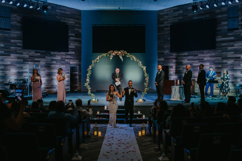 bride and groom hold hands during the recessional