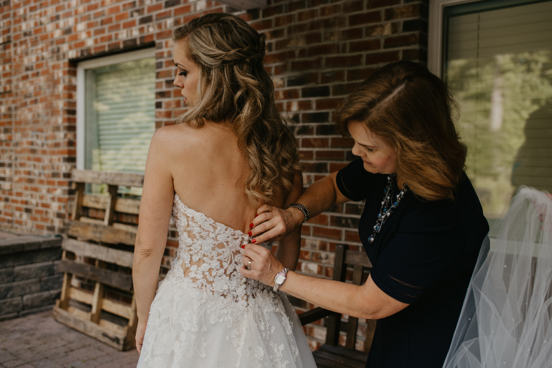 Mom doing up the bride's dress for her
