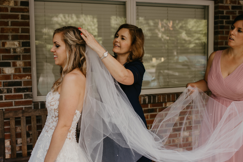 Mom and sister helping the bride put on her cathedral veil at an outdoor wedding in New York