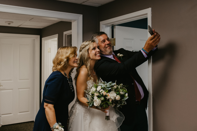 Bride takes a selfie with her parents before the wedding