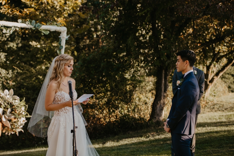 Outdoor wedding ceremony in New York with bride reading her own vows