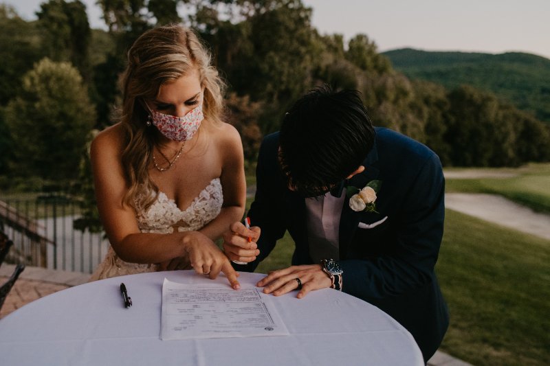 bride and groom wear facemasks as they sign the paperwork