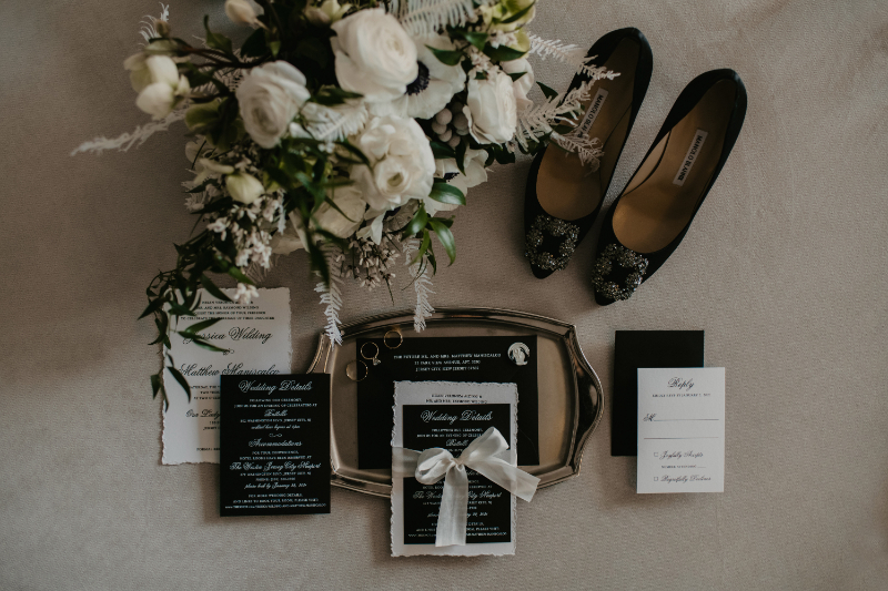 detail flat lay with invitations, shoes and rings