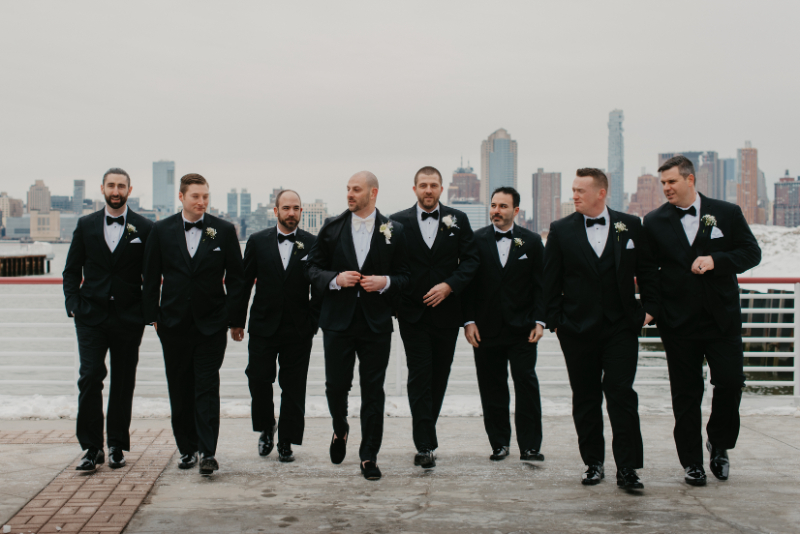 groom and groomsmen taking photos in front of new jersey waterfront