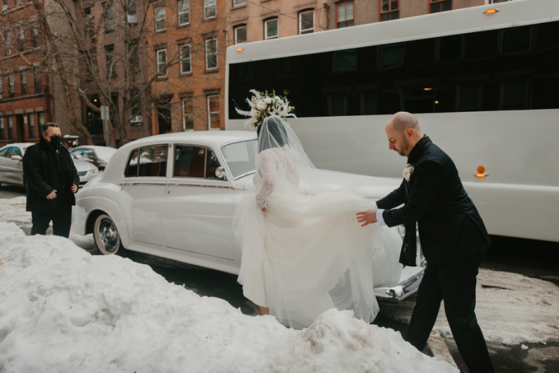 groom carrying brides dress to the car