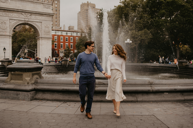 engagement photos in front of a fountain in washington square park
