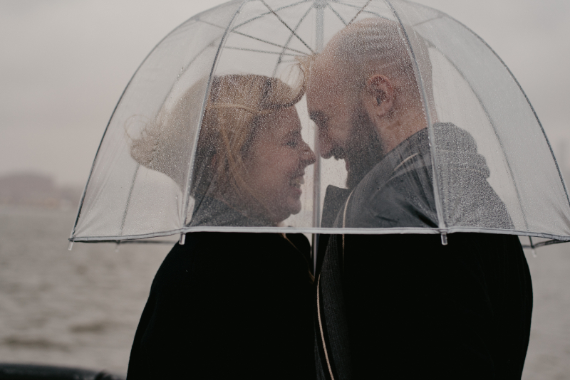 Clear umbrellas with couple kissing underneath