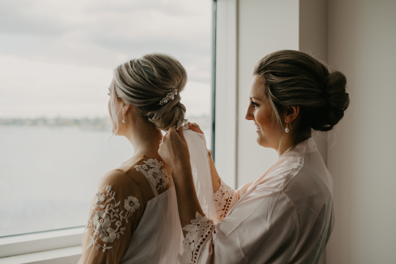 Sister helps bride put on veil during getting ready photos