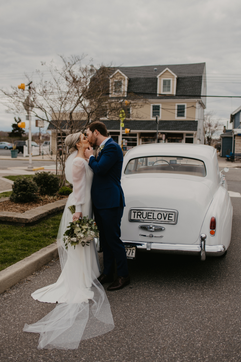 Bride and Groom stand outside in New Jersey with getaway car