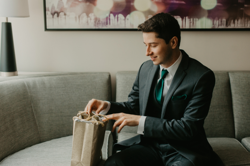 groom getting ready photos with gift from bride