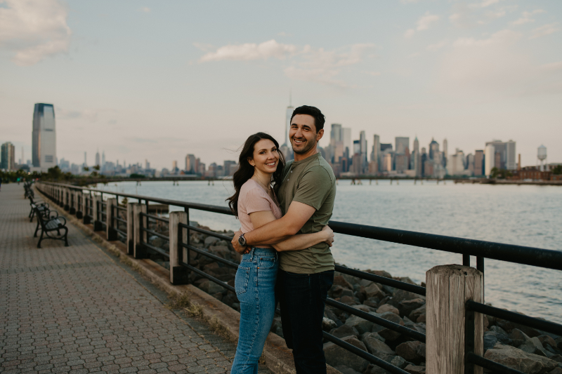 Casual engagement photo outfits in front of New Jersey waterfront with NYC skyline